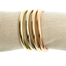 Cuffling bracelets in four gold alloys -- green, white, yellow and rose -- by contemporary jewelry designer Marla Aaron
