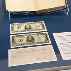 High denomination US currencies on view alongside check signed by JFK and autographed first copy of the first edition of