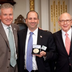 MoAF Chairman Richard Sylla and President David Cowen receive closing bell medallions from NYSE Euronext CEO Duncan Niederauer. Photo courtesy of Valerie Caviness.