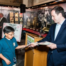 Alexander Burns hands out stock certificates to students at the launch of the Free Saturday program.