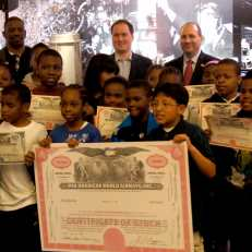 Students from PS 66 in Brooklyn show off their stock certificates.